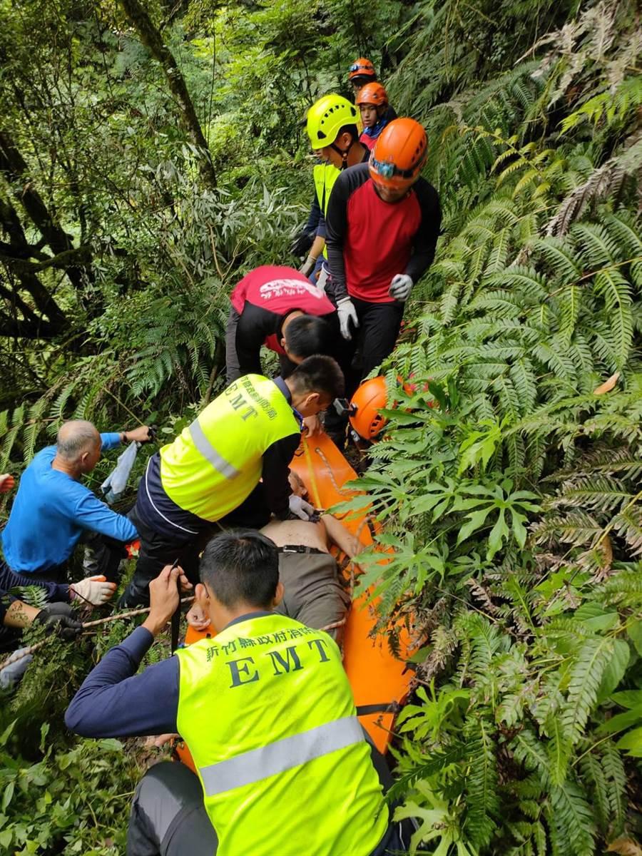 尖石鎮西堡巨木群發生登山客跌落山谷意外,救難人員將已無生命跡象的67歲老翁抬上搭架。(消防局提/羅浚濱新竹傳真)