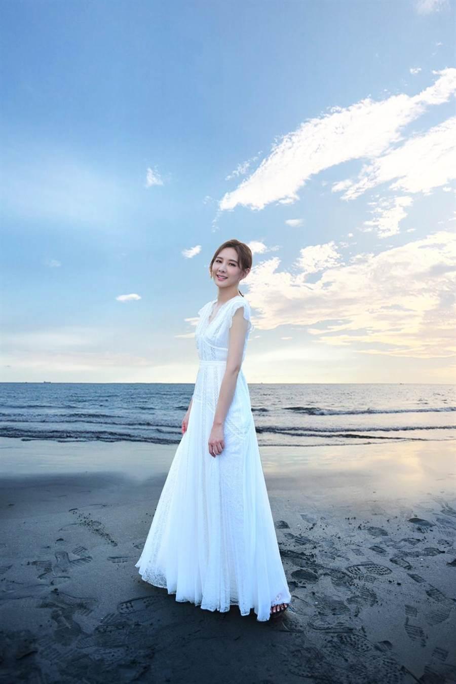 安心亞身著白色洋裝漫步在漁光島沙灘。(環球音樂提供)