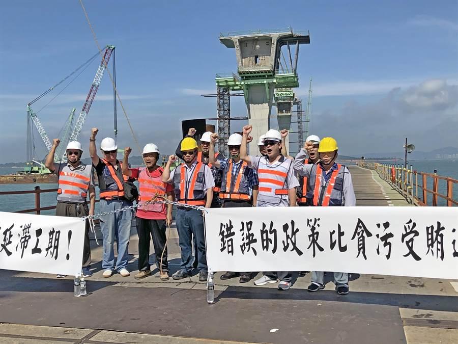 國登營造在施工棧橋拉白條,抗議3標承商東丕營造占用該公司留置工地的機具設備。(李金生攝)