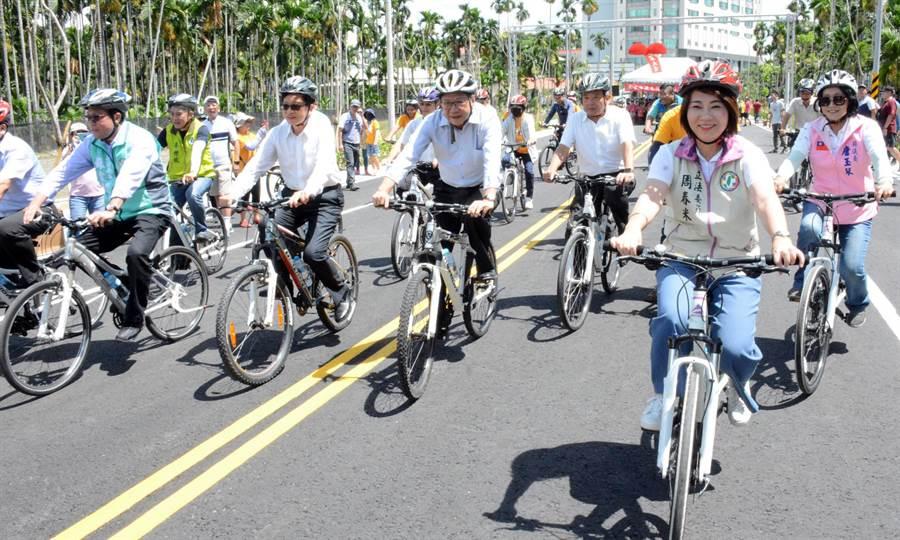 屏東市瑞光路延伸工程27日正式通車,屏東縣長潘孟安(中)與地方各級民代騎乘單車體驗。(林和生攝)