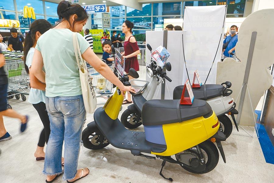 財政部表示,車輛移動汙染源是造成台灣空汙主因之一,因此必須負擔貨物稅,引爆機車族怒火,紛紛上網開嗆。圖為大賣場內擺了兩部電動機車,逛街民眾不免多看幾眼。(本報資料照片)