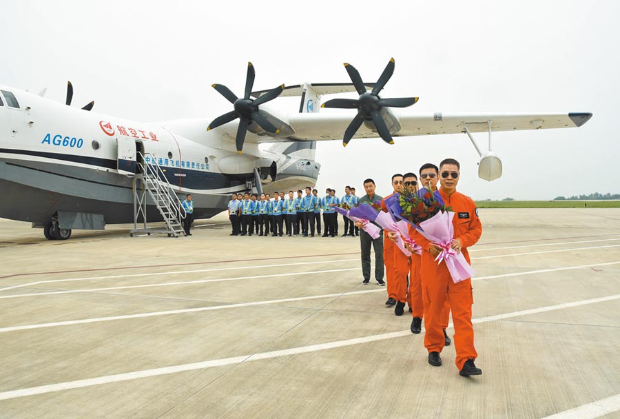 7月26日,AG600機組人員在進行海上首飛後,走下飛機。(新華社)