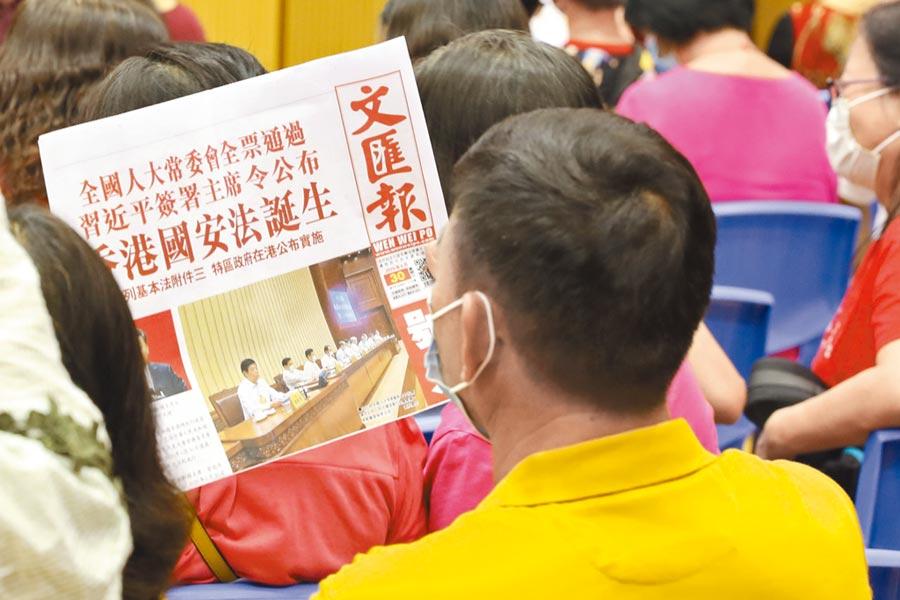 7月1日,香港市民閱讀報紙上有關香港國安法的新聞。(中新社)