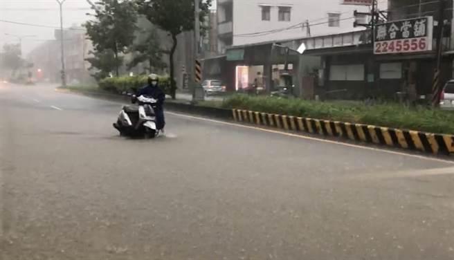 婦人騎車行 積水路段拋錨,在水中推車前進!(廖志晃攝)