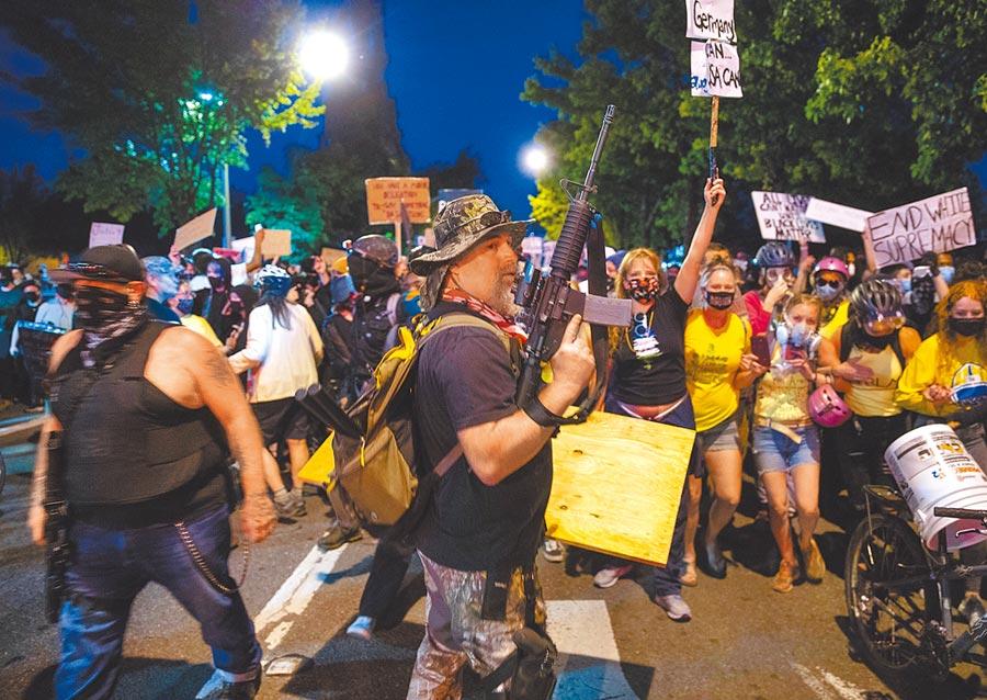 美國奧勒岡州波特蘭的「黑人的命也是命」示威活動中,有一批婦女組成人牆,她們自稱是「媽媽之牆」(Wall of Moms),戴著口罩,高舉標語,大力抗議川普派遣「聯邦特警隊」至現場鎮壓。(美聯社)