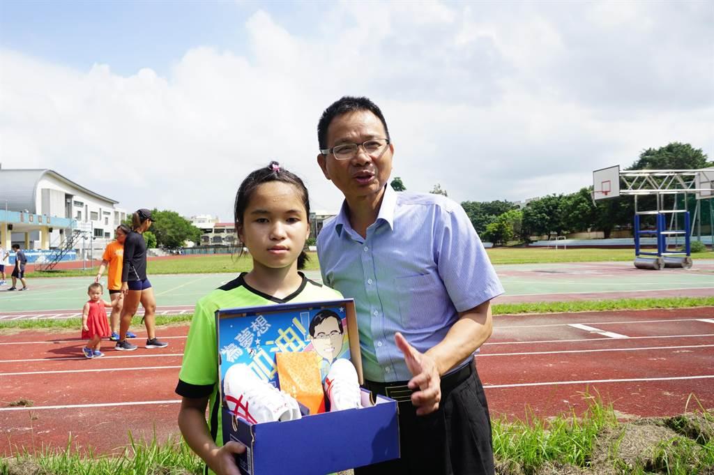 台中市身心障礙體育總會理事長陳清龍(右)致贈全盲運動員吳宜容(左)比賽專用釘鞋和紅包。(王文吉攝)