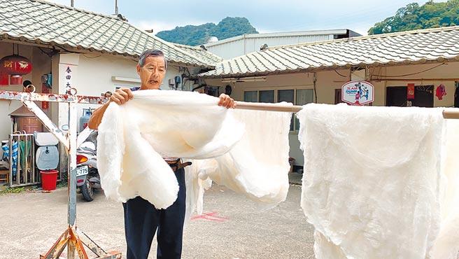 泉明生態教育蠶業農場負責人涂泉明,用手拉扯真蠶絲說明延展性。(巫靜婷攝)