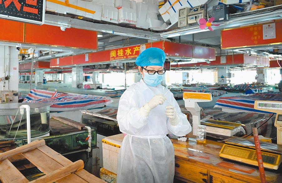 6月19日,廣西南寧市富德海鮮批發交易市場內,疫情監測組工作人員對生鮮銷售攤點進行外環境採樣檢測。(中新社)