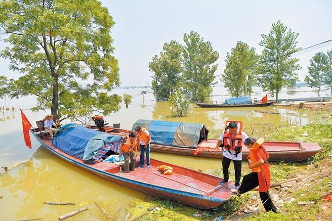 長江水位漸消退,7月24日,江西鄱陽縣昌洲鄉馬湖村的村民們登船準備回家拿取物品。(新華社)