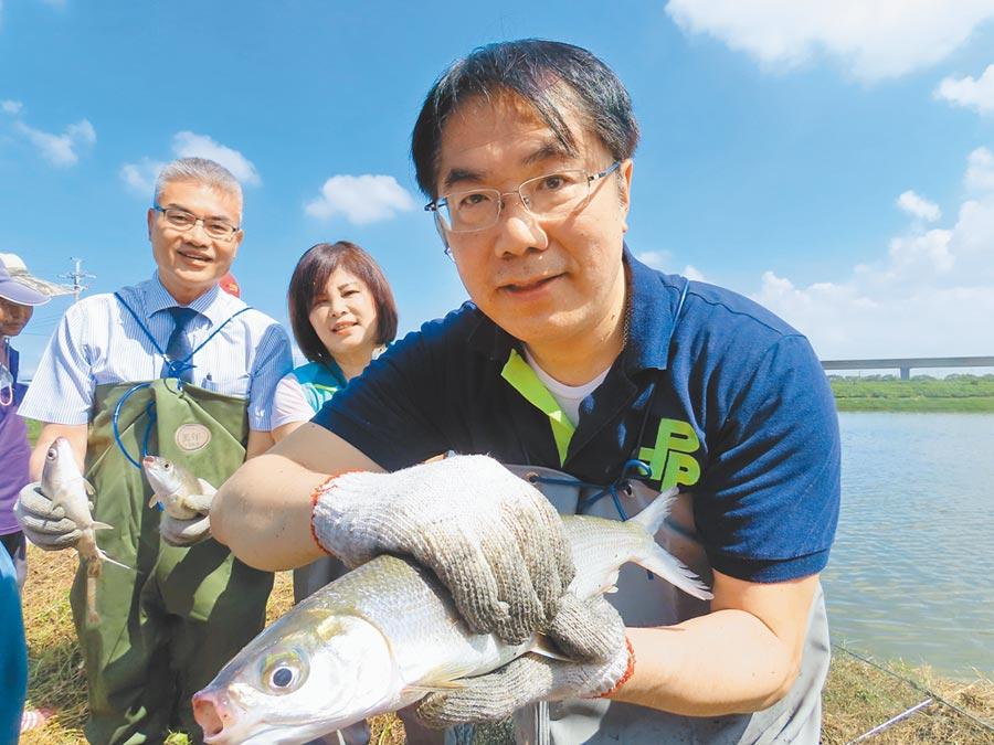 虱目魚產季即將到來,台南市長黃偉哲29日(右)到產地之一的學甲參訪,也下水捕撈「尚鮮」的虱目魚。(莊曜聰攝)