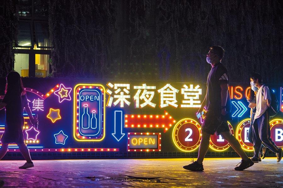 「北京消費季」重啟,圖為7月28日晚間,市民走過朝陽區望京的一處餐飲集中地彩燈招牌。(中新社)