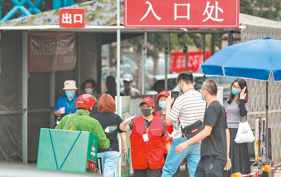 北京市昌平區一社區27日出現確診病例後封閉。圖為29日社區口工作人員勸阻外送員進入。(中新社)