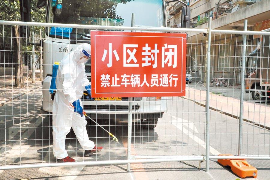 7月29日,大連市中風險地區的社區實施封閉管理,並有工作人員在門口進行消毒。(中新社)