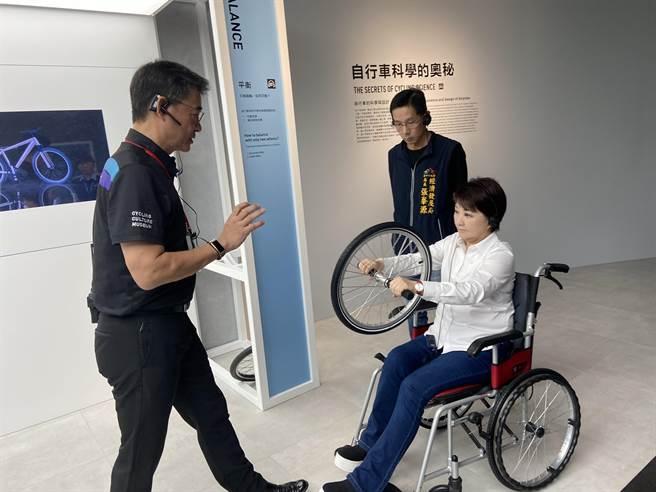 台中市长卢秀燕亲自体验「陀螺效应」,当车轮转动时,轮子就像是颗转动的陀螺,陀螺效应就是让自行车保持平衡与否的自然物理现象。(卢金足摄)