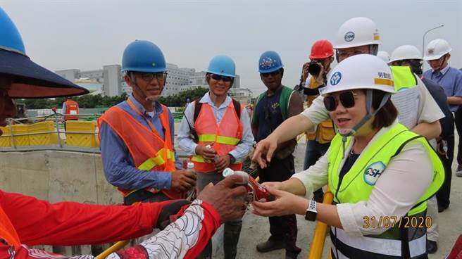劳动部许铭春与台积电第18厂新建工程致赠冰凉饮料慰劳现场作业劳工。图/台积电提供