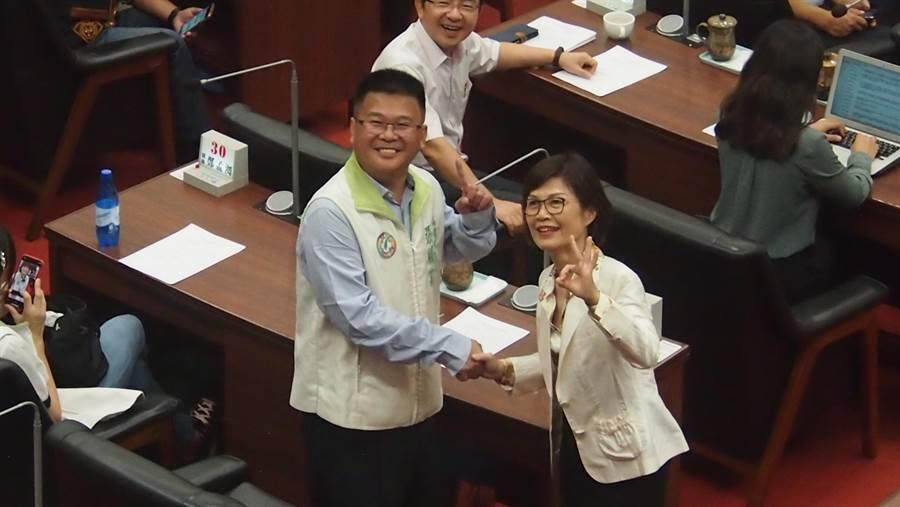 高雄巿議會議長補選,藍、綠兩大黨團推派的曾麗燕、張勝富在投票前先禮後兵握手,並各自比出巿長補選候選人的號碼。(圖/曹明正攝)