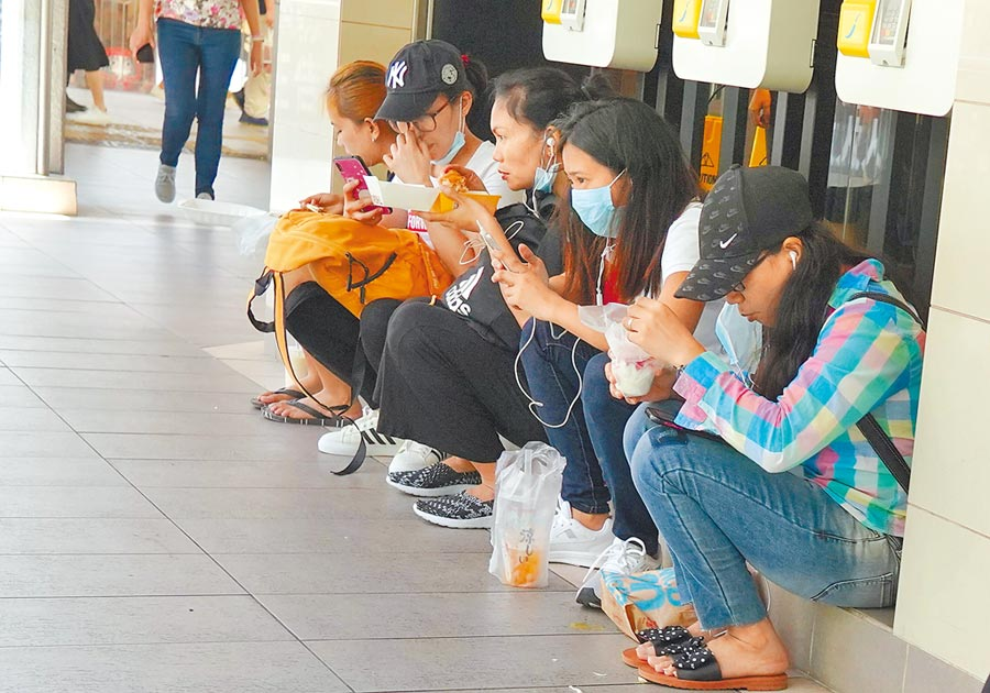 7月30日中午,一些食客聚集在香港灣仔一間快餐店門口進餐。(中新社)