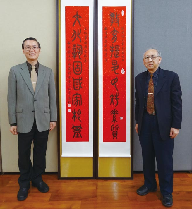 書法家洪啟義(右)受教育部邀請書寫政策標語,與教育部前秘書處處長周以順(左)合影。圖/洪啟義提供