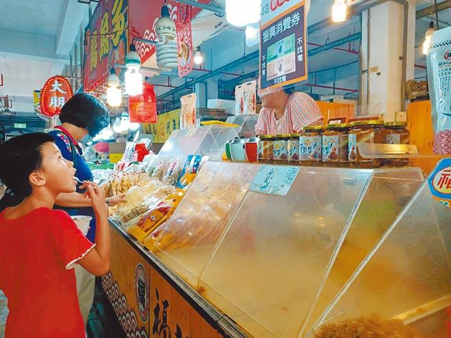 嘉義縣一名男童跟著家人採買魚貨,盯著店家張貼的振興三倍券使用標語。(張毓翎攝)