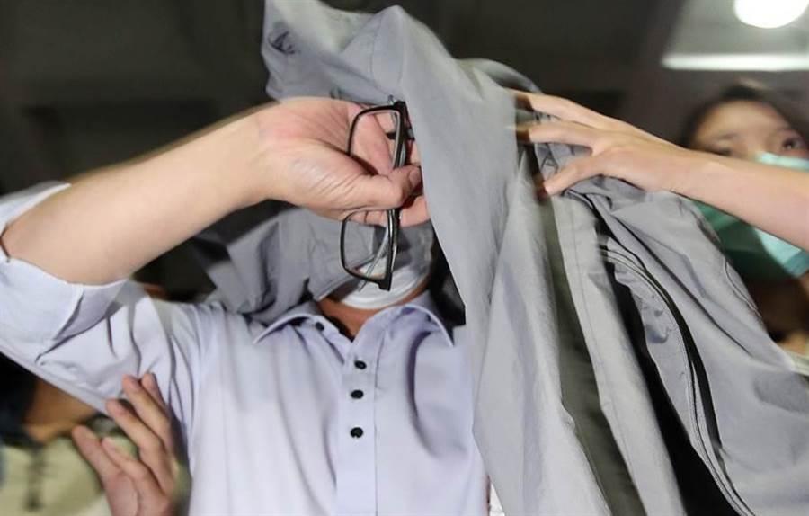 立委趙正宇被移送北檢時,脫下外套蓋住頭部,相當狠狽。(中時資料照)