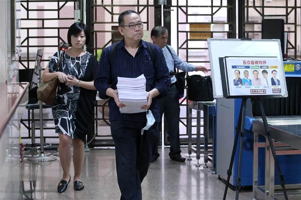 李恆隆委任律師杜英達(中)抱著一疊卷證離開。(黃世麒攝)