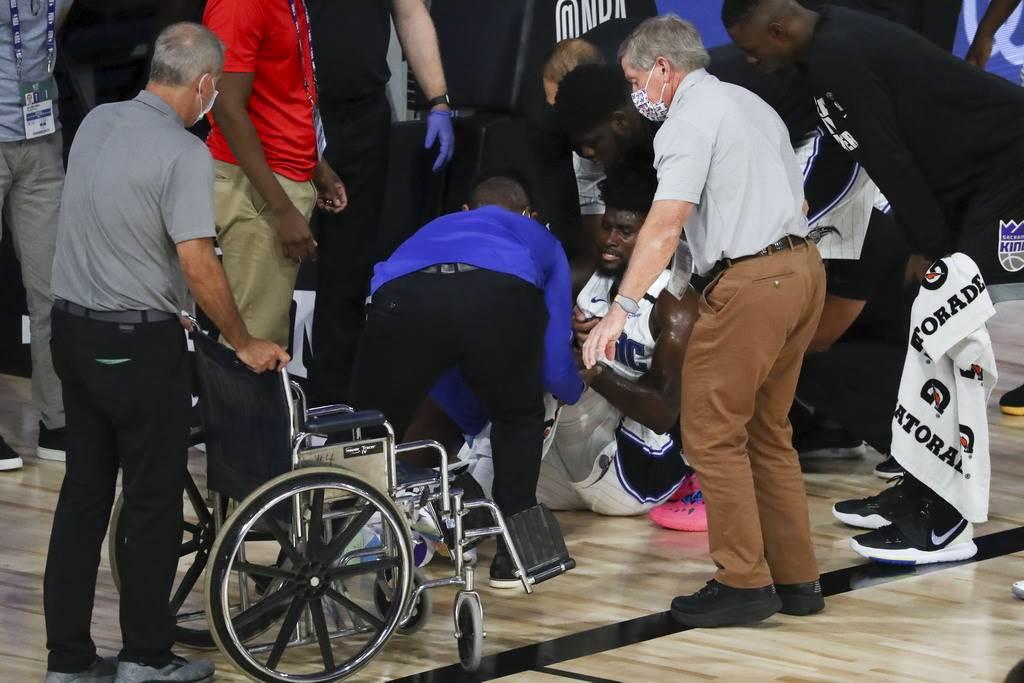 左膝嚴重扭傷的艾薩克,只能用輪椅抬他出場。(美聯社)