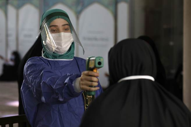 伊朗一名志願者身穿防護服給民衆測體溫。(美聯社)