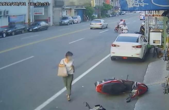 白色轎車車主下車後,看著倒地機車,邊走邊笑。(截自《新竹爆料公社》)