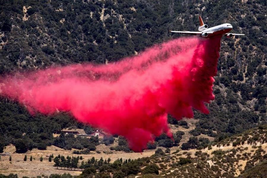 飛機緊急升空撒下阻燃劑。(圖/達志/美聯社)