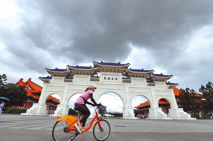 受到颱風哈格比接近影響,2日大台北地區午後雲層漸漸增多,圖為民眾騎腳踏車經過中正紀念堂牌樓。(劉宗龍攝)