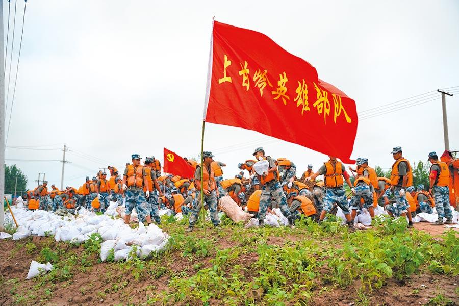7月13日,解放軍中部戰區官兵裝填沙土石,加固湖北沙套湖子堤。(新華社)