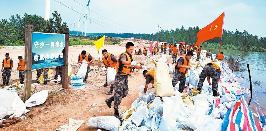 7月14日,解放軍東部戰區官兵火速馳援抗洪一線,加固江西九江市圍堤800多公尺。 (新華社)