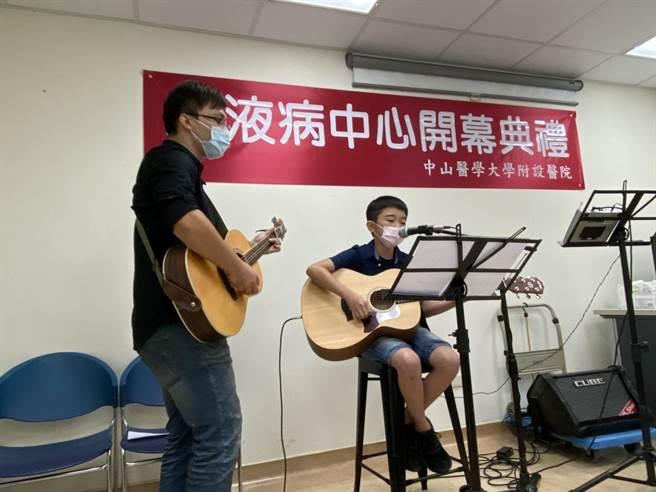 12歲重度血友病患李小弟在中山附醫血液疾病中心成立會上輕快的彈著吉他演唱蘇打綠的歌曲。(馮惠宜攝)