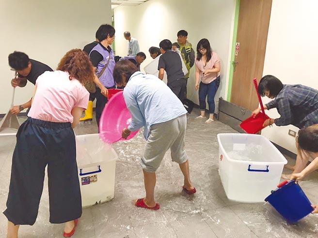 台北兒童新樂園內的兒童劇場,因大雨造成劇場外水管爆裂,讓承租單位如果兒童劇團連帶受到波及,劇團人員緊急拿容器將雨水往外撈出。(如果兒童劇團提供)