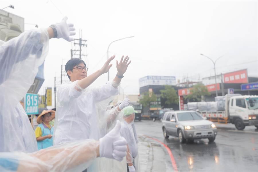 民進黨高雄市長候選人陳其邁穿雨衣站在高雄市仁武區鳳仁路及澄觀路口,向路過的民眾拜票,珍惜每一個與市民接觸、交流的機會。(林雅惠攝)