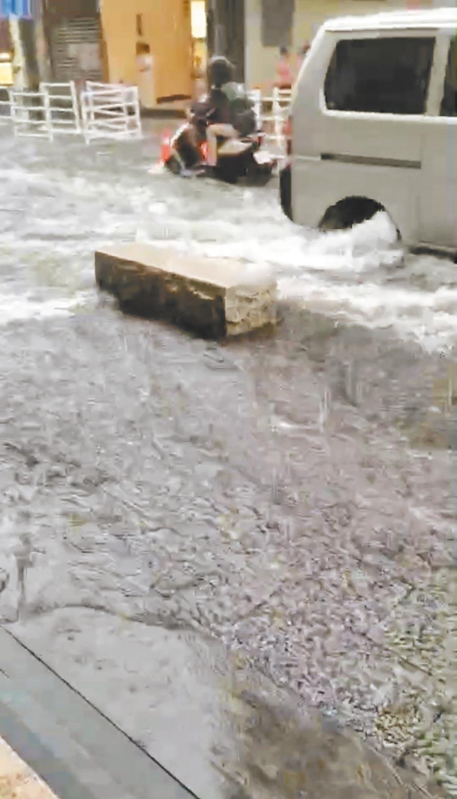 淡水老街淹大水,不少店家担心水愈淹愈高,酿成灾情,拉下铁门暂停营业。(民眾提供/戴上容新北传真)