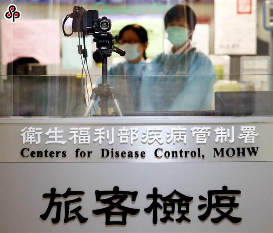 圖為桃園機場第二航廈入境管制區發燒篩檢站內,2名疾管署防疫人員利用紅外線體溫感測器檢測旅客體溫。圖/本報系資料照