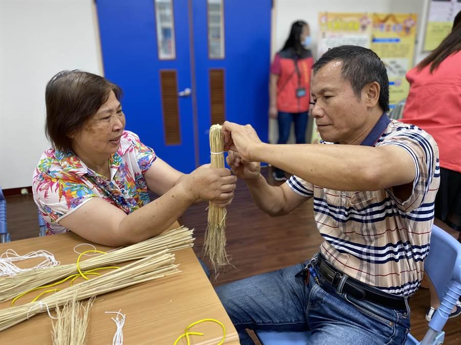 大湖鄉衛生所社區營造健康委員會主委徐鐵龍(右),初次嘗試自製稻稈雙節棍,直說不會很難。(巫靜婷攝)