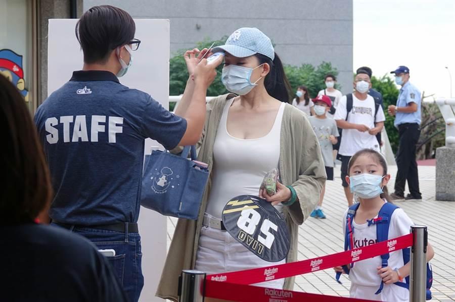 桃園棒球場的進場觀看球賽球迷每個人在入場時都戴上口罩,工作人員也會幫球迷量測體溫。(陳麒全攝)