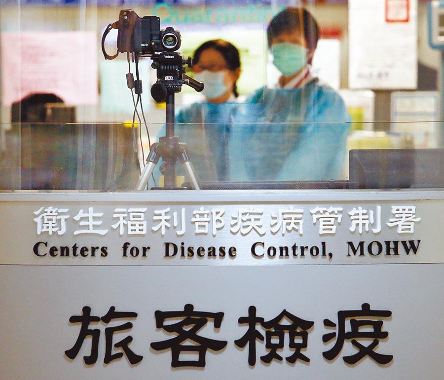 日本疫情升溫!指揮中心:自中低感染風險國家移除。圖為機場防疫人員利用紅外線體溫感測器檢測旅客體溫。(本報資料照片)