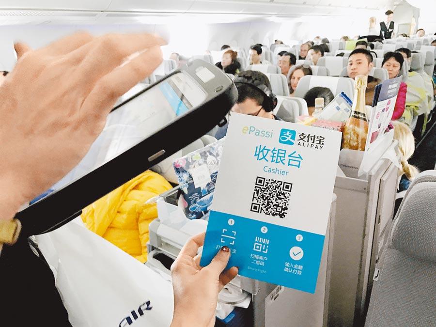 北京至芬蘭赫爾辛基的航班上,空服員透過支付寶收取貨款。(新華社資料照片)