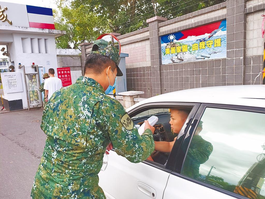 宜蘭金六結營區門口的衛兵對要進入營區的人員仔細量測額溫,同時噴灑酒精消毒。(胡健森攝)