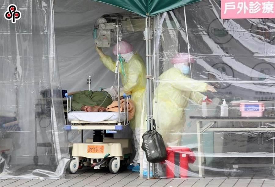 圖為台北市某醫院戶外診療區內,醫護人員著隔離衣使用移動式X光機進行檢查。(圖/本報資料照片)
