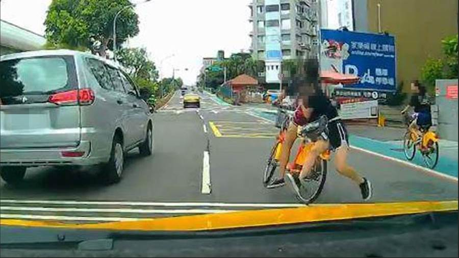 短褲少女Youbike雙載,突然不穩歪斜,附載的那名少女跳車,後方目擊小黃司機嚇壞驚呼:「放暑假比鬼門開可怕」。(照片來源:臉書社團《爆料公社》)