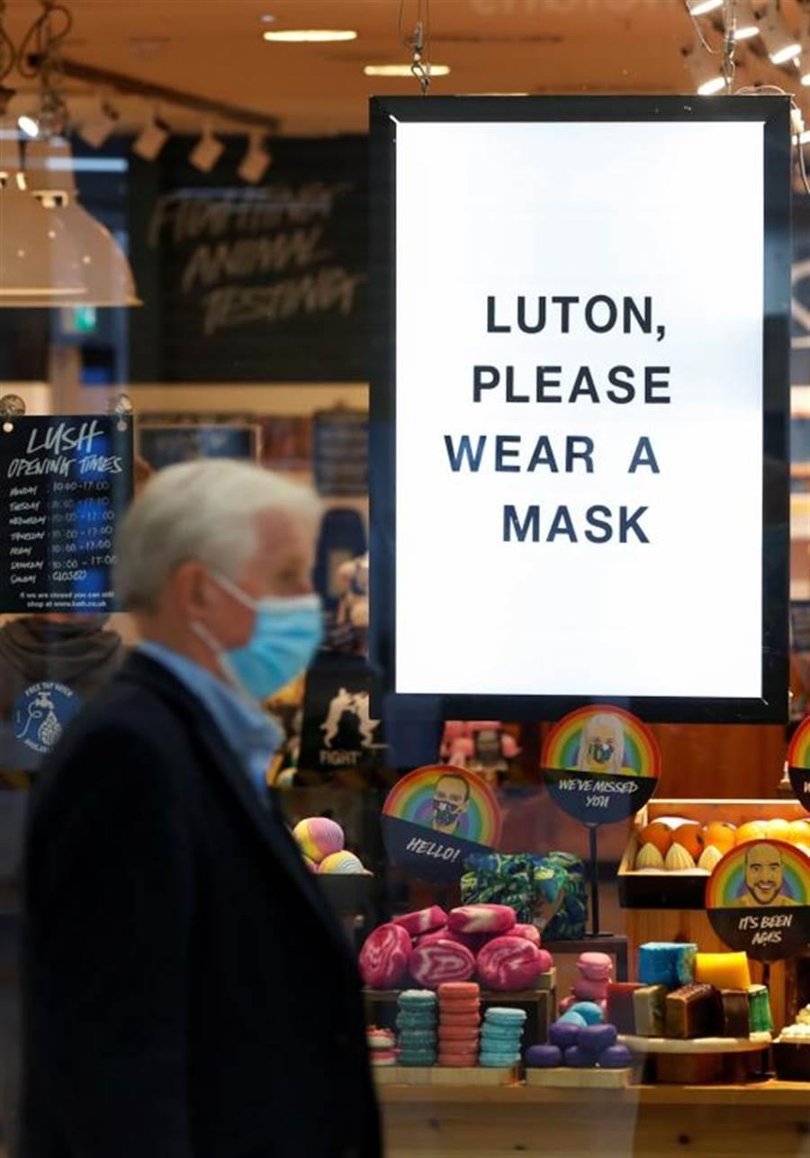 英國部分區域的室內場所,已全面強制戴口罩。圖為英格蘭東部的盧頓(Luton),店家掛上大幅海報,要求消費者戴口罩。(路透)