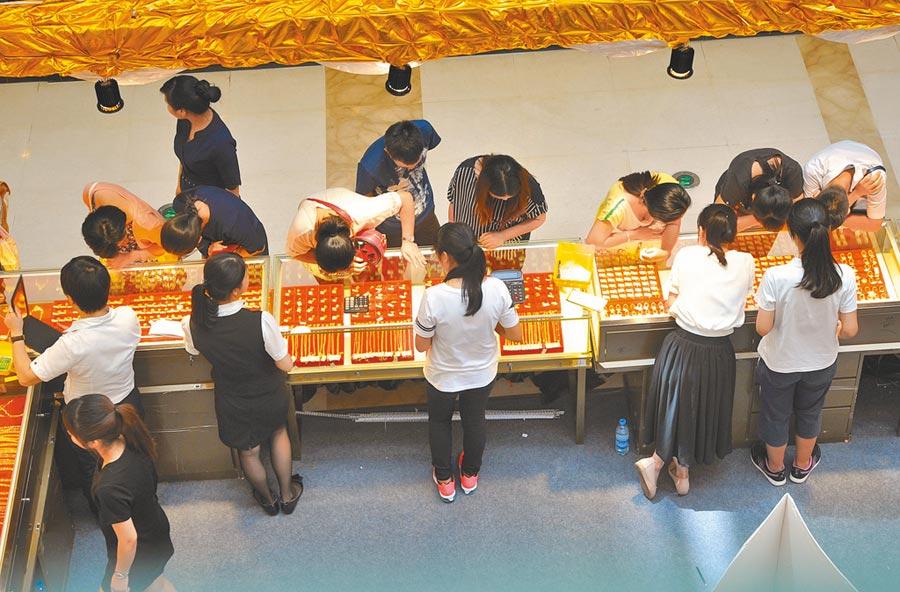 大陸購金族年輕化,圖為福州市民在商場購買黃金飾品。(中新社資料照片)