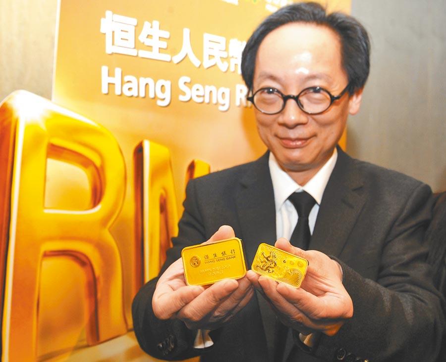 黃金ETF被追捧,圖為恒生銀行在2012年推出全球首支人民幣黃金ETF,恒生執董展示金條。(新華社)