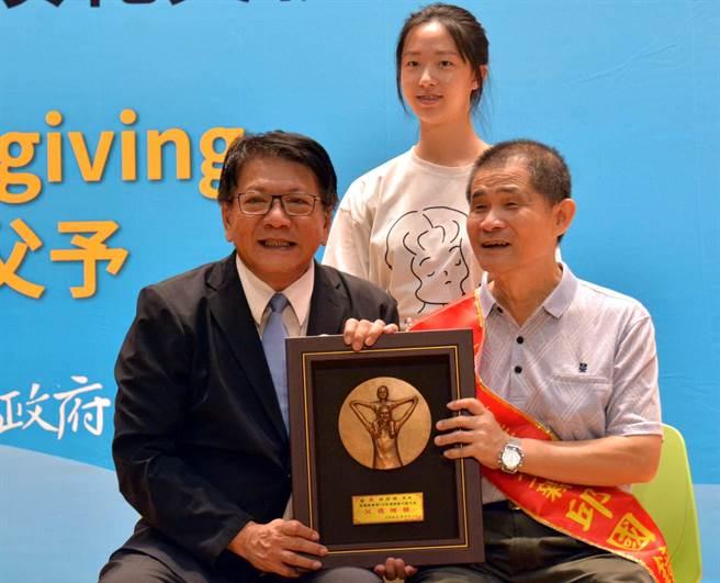 63歲邱國鐘(前右)是視障者,樂觀的他努力學習,成為國內第一位盲人調音師,今年受表揚為模範父親。(潘建志攝)