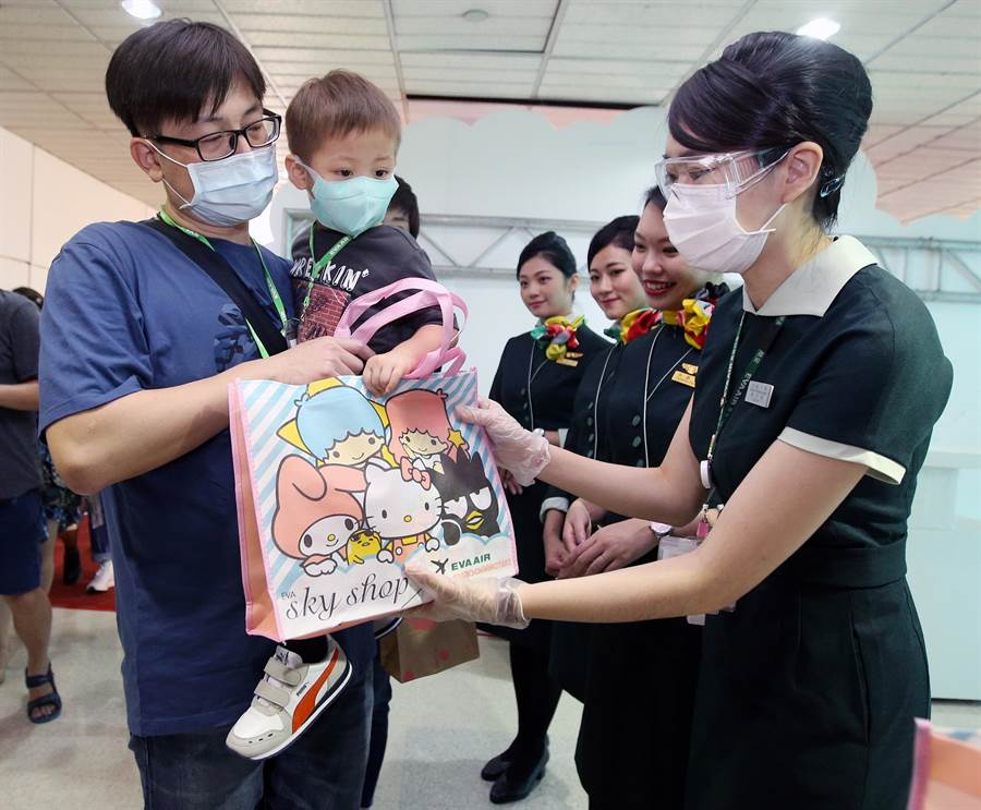 登機前地勤人員致贈紀念禮品給旅客。(范揚光攝)
