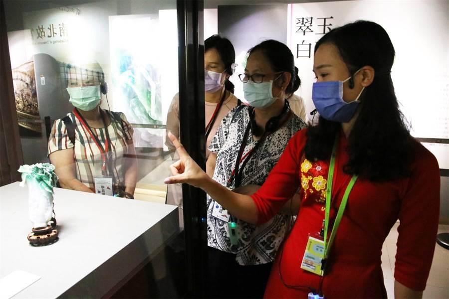 越南新住民范氏月(右1)指出翠玉白菜只有18公分高,但卻雕工精細,令人陶醉。(移民署提供/李文正台北傳真)